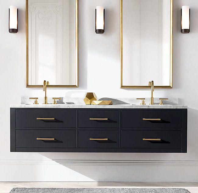 black floating cabinet, golden handler, golden faucet, white marble top, golden lined mirror, white wall, sconces