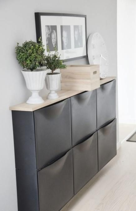 black floating cabinet, wooden top, white wall, wooden floor