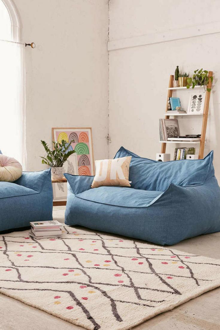 blue bean bad, white floor, white rug, white wall, wooden shelves