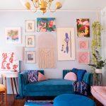 Blue Velvet Sofa, Blue Velvet Round Ottoman, Pink Cushion, Wooden Floor, White Console Table, Paintings, Colorful Rug