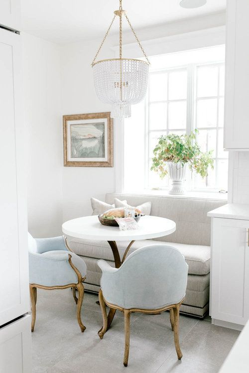 breakfast nook, grey bench, blue chairs with golden lines, white round table, grey floor, chandelier