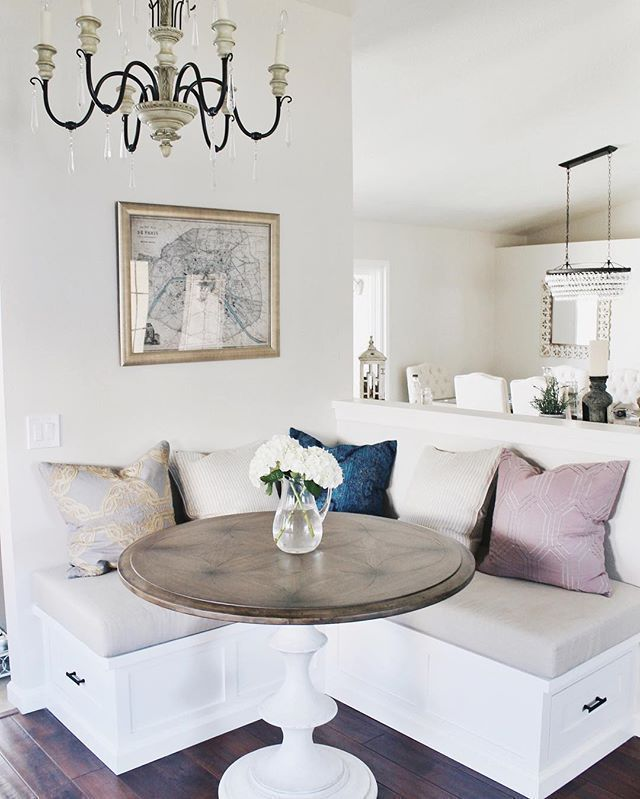 breakfast nook, white bench with white cushion, white wall, chandelier, round table, wooden floors