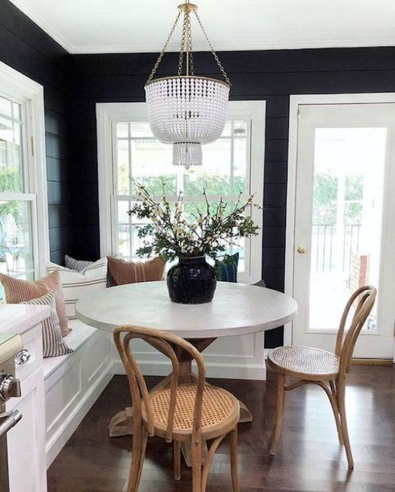 breakfast nook, wooden floor, black wooden wall, white built in bench, pillows, white round table, rattan chairs, chandelier