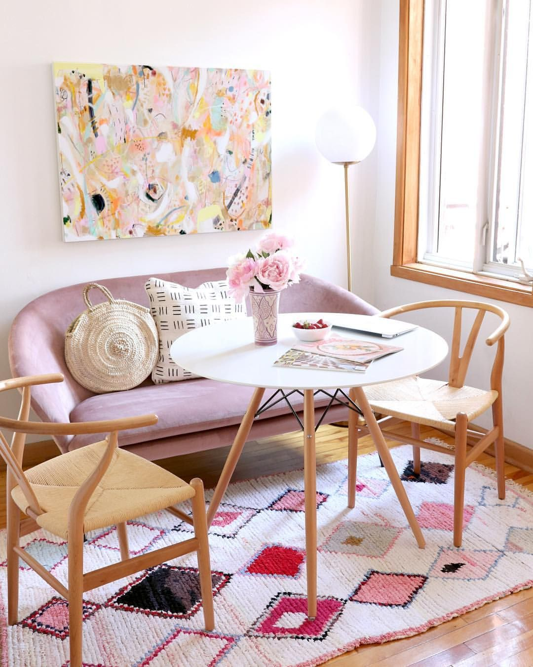 breakfast nook, wooden floor, wooden chairs with rattan seat, white round table, pink velvet sofa