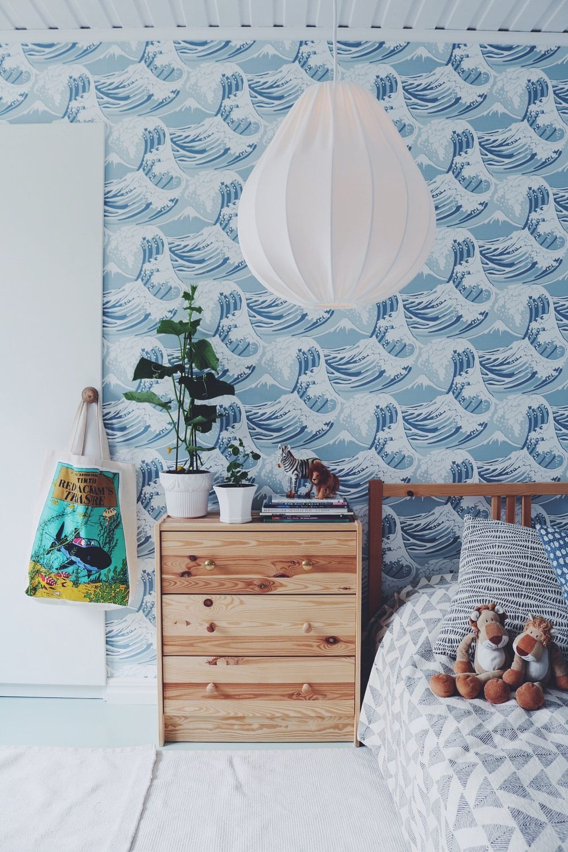 child bedroom, white floor, white rug, woode side cabinet, wooden bed platform, white paper pendant, blue wallpaper
