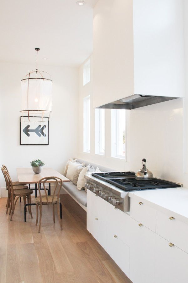 dining nook, wooden floor, white wall, white penant, white floating bench, wooden table, wooden chairs, white kitchen cabinet, hood