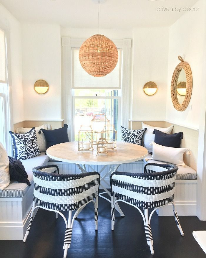dining room, black floor, white wall, rattan pendant, white built in bench, whtie black rattan, round wooden table