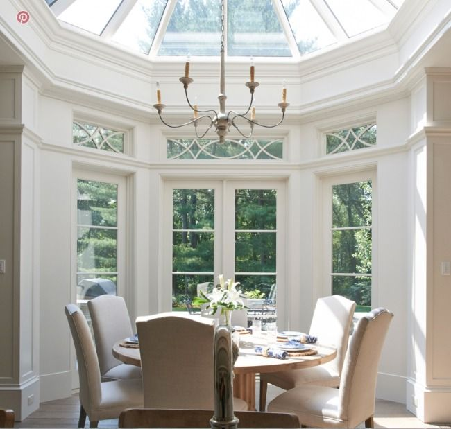 dining room in the oval space, white wall, glass ceiling, glass window, round wooden table, brown chairs
