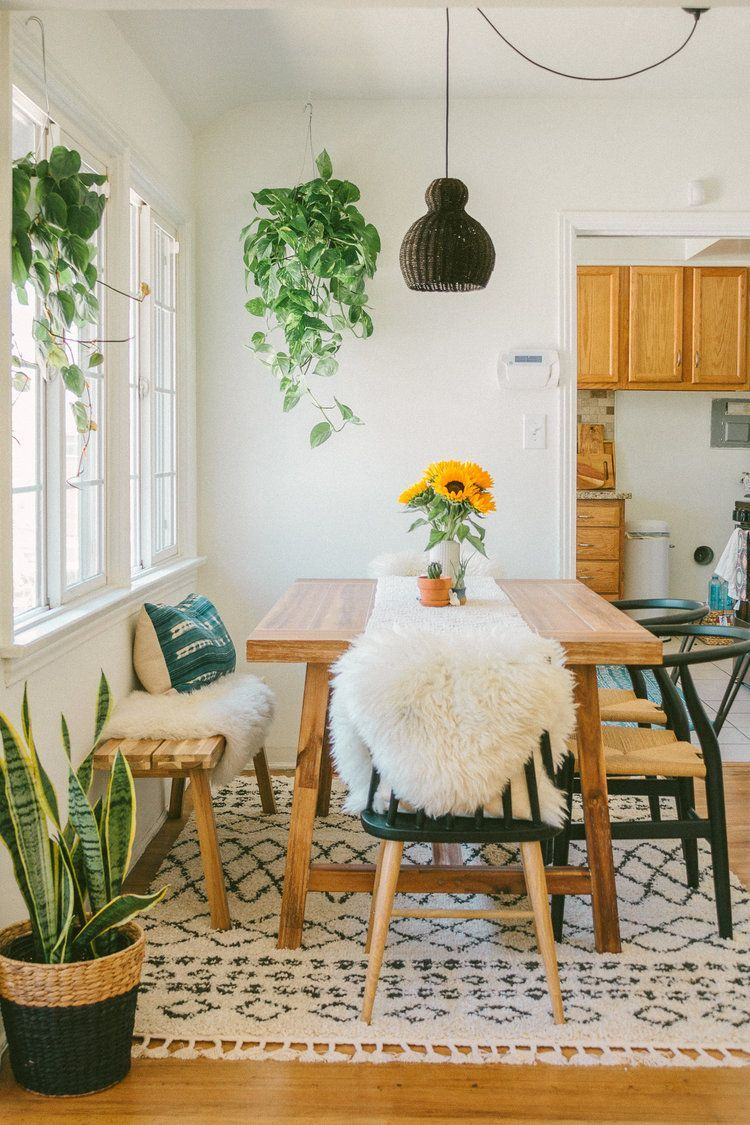 dining room, white wall, wooden floor, patterned rug, wooden table, wooden bench, black wooden chairs, black rattan pendant