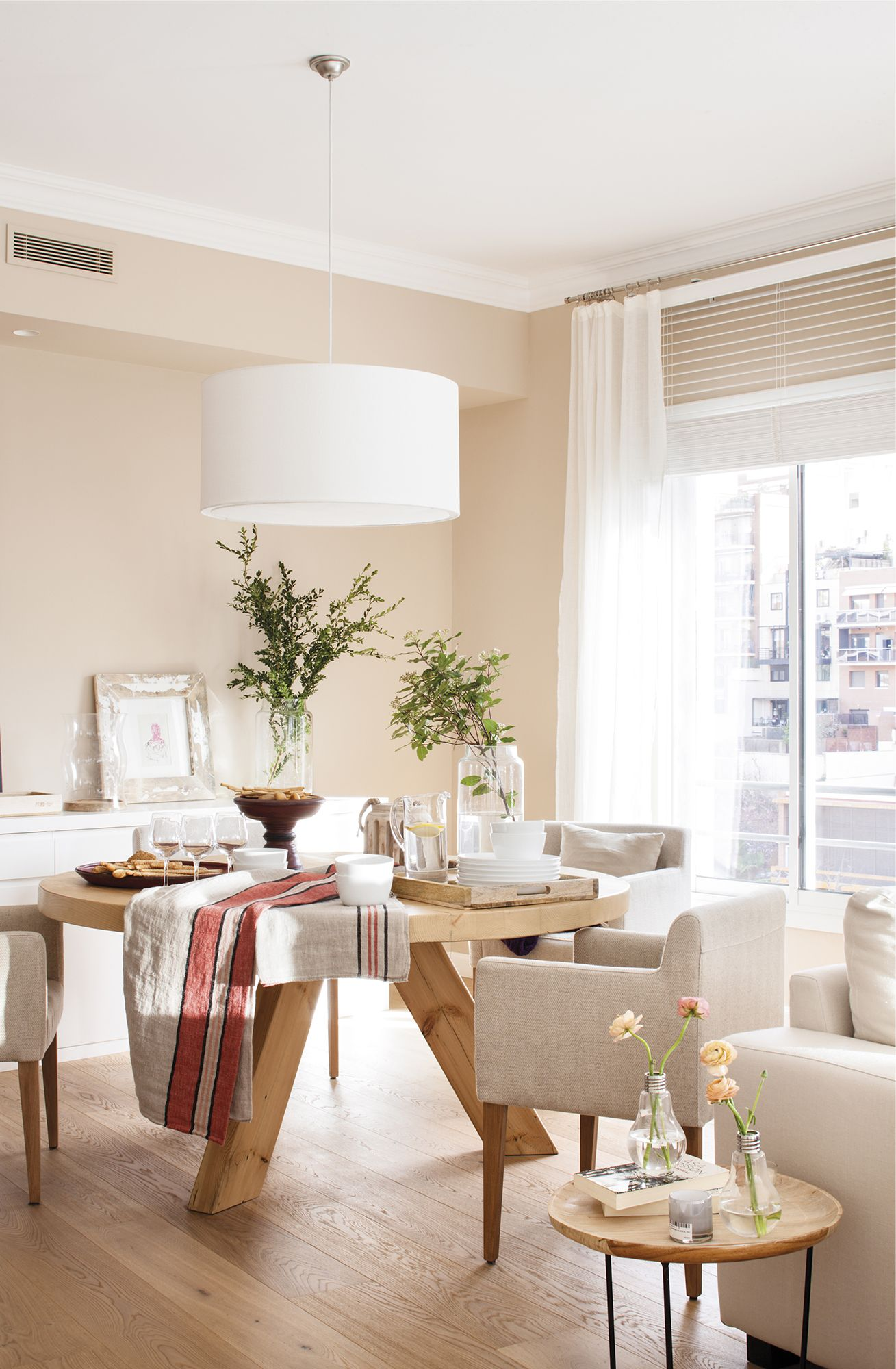 dining room, wooden floor, cream wall, wooden round table, grey chairs, white pendant, white cabinet