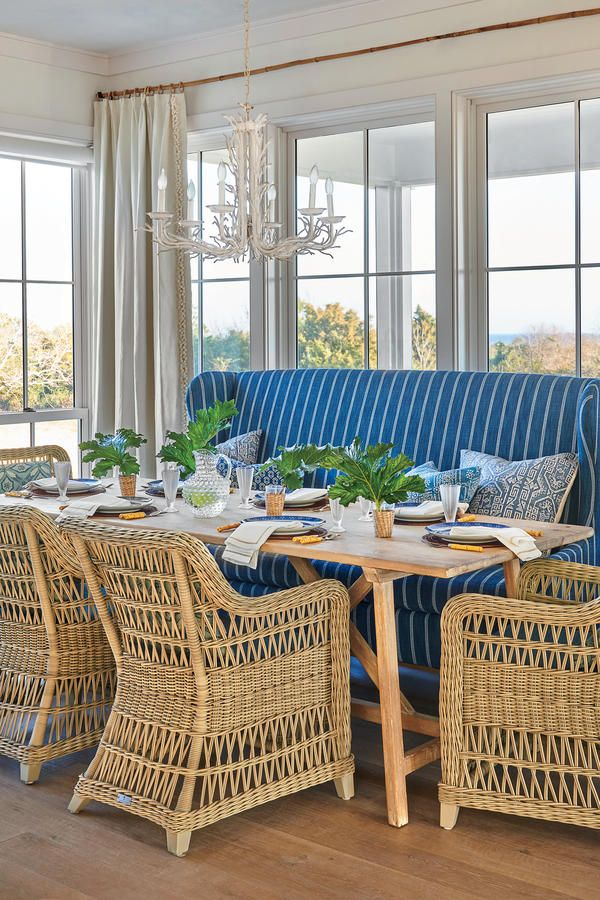 dining room, wooden floor, rattan chairs, blue sofa, wooden table, glass window