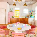 Dining Room, Wooden Floor, White Round Table, Pink Chairs, White Subway Wall, Wooden Island With White Top, White Cabinet, Yellow Framed Window, White Floating Shelves