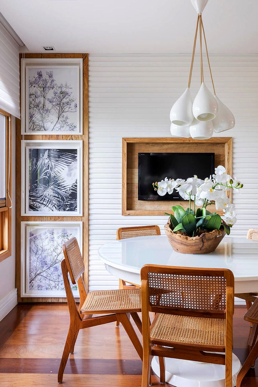 dining room, wooden floor, white round table, wooden rattan chairs, white pendants, white wall