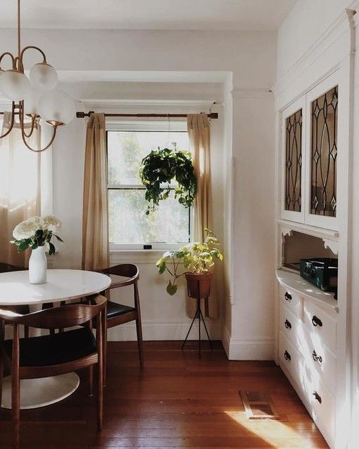 dining room, wooden floor, white wall, white cabinet, white round table, black chairs, white pendant