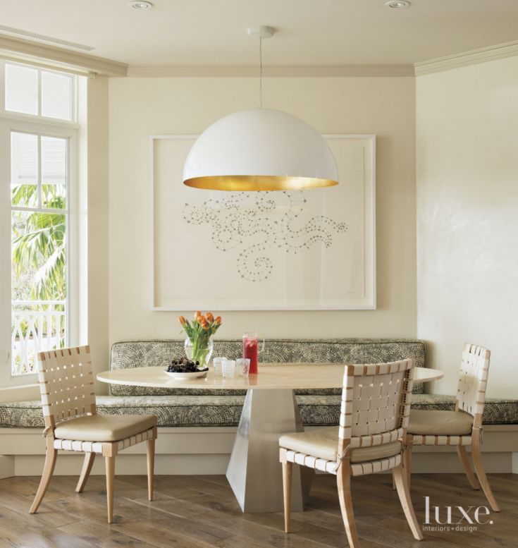 dining room, wooden floor, white wall, white half round pendant, white bench with patterned cushion, white oval table, white chairs