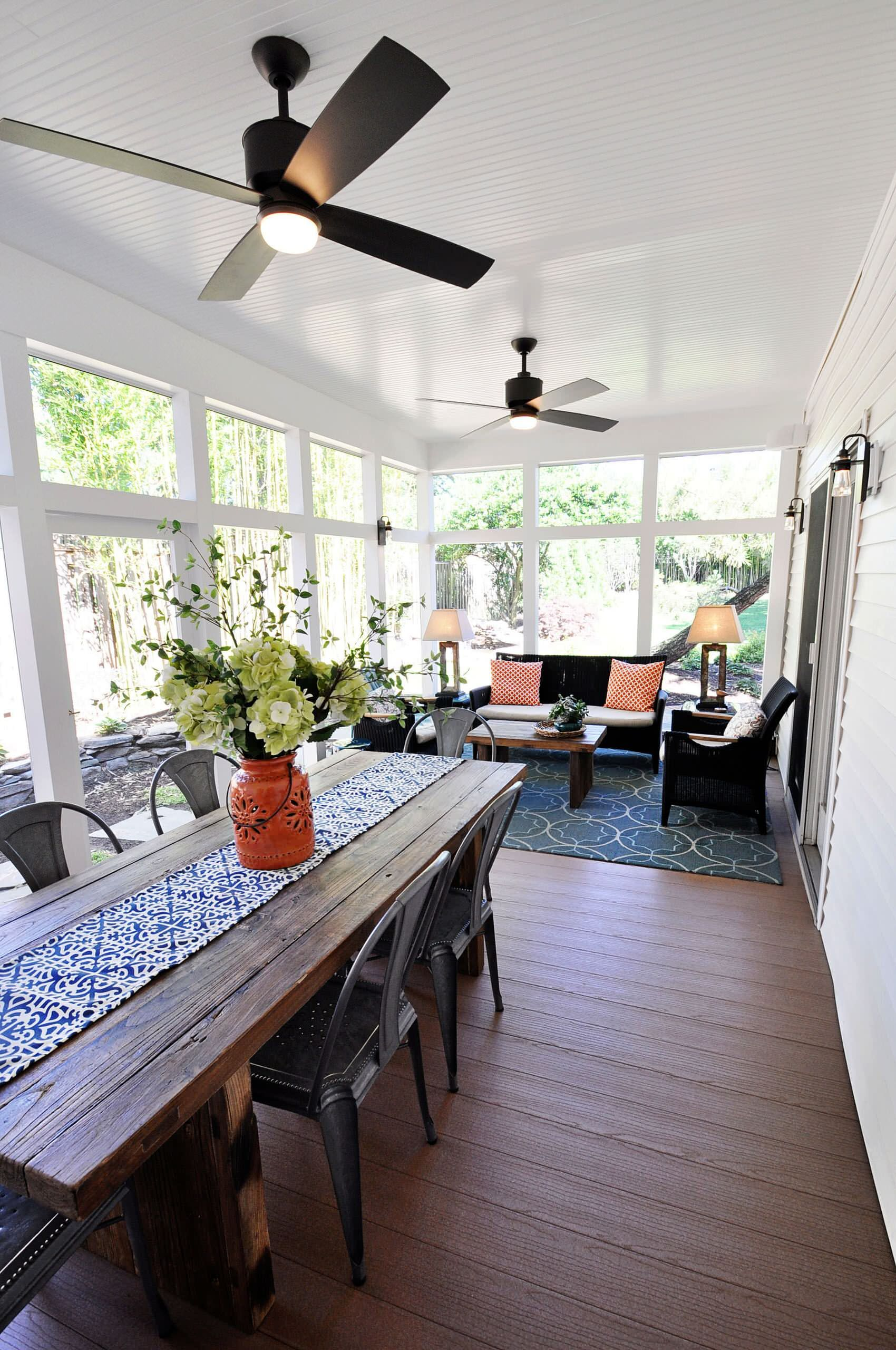 dining room, wooden floor, white wooden wall, wooden table, black chairs, wooden dining set, blue patterned rug, white wooden ceiling, black ceiling fan