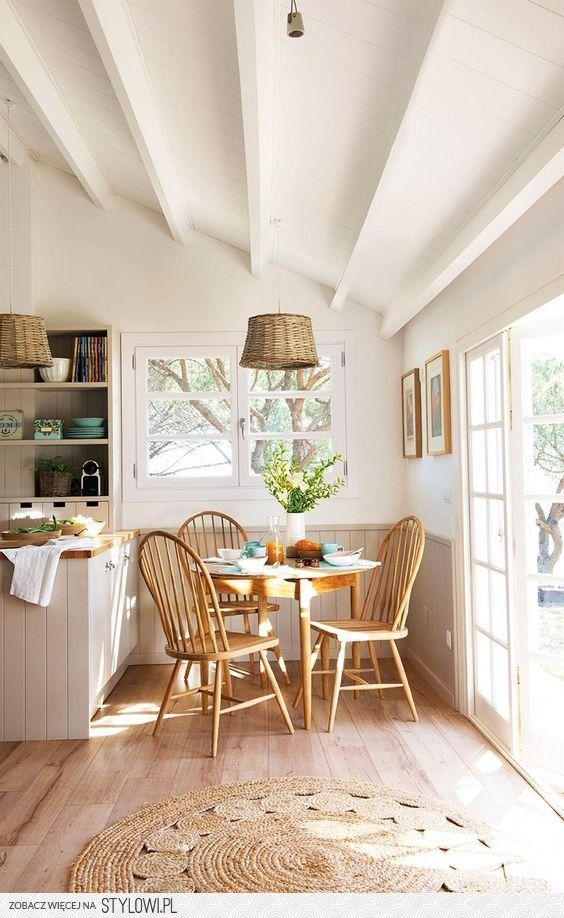 dining room, wooden floor, wooden wainscoting, white wall, wooden chairs, wooden table, rattan pendant