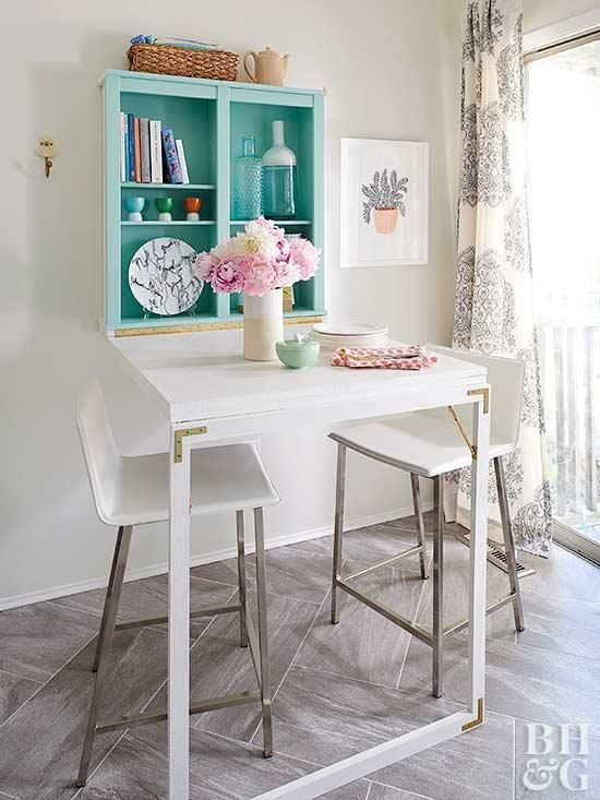 dining set, grey floor tiles, white built in table, white square stools, green shelves, patterned curtain