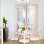 Dining Set, Wooden Floor, Golden Lined Chairs With White Cushion, White Wall, Pink Doors, White Pendants, Black Cabinet