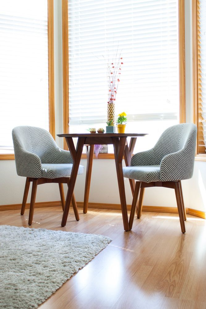 dining set, wooden floor, white wall, wooden round table, modern chairs with striped cushion