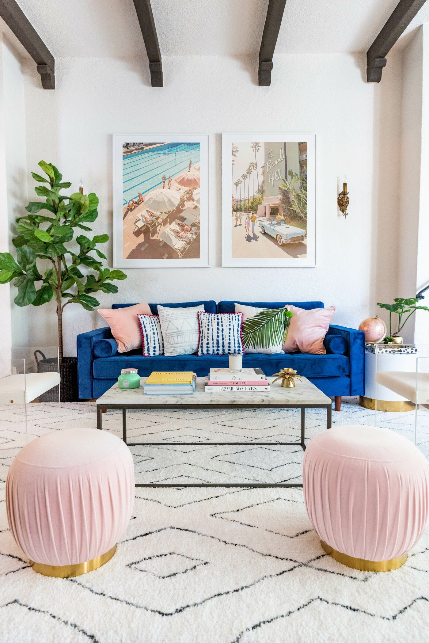 electric blue velvety sofa, white patterned rug, pink ottomans, white wall, white mable coffee table