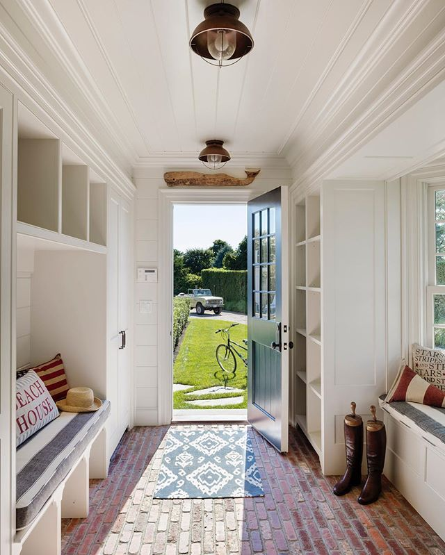 entryway, brick floor, white wooden shelves, blue door, white wooden bench, striped cushion, window bay