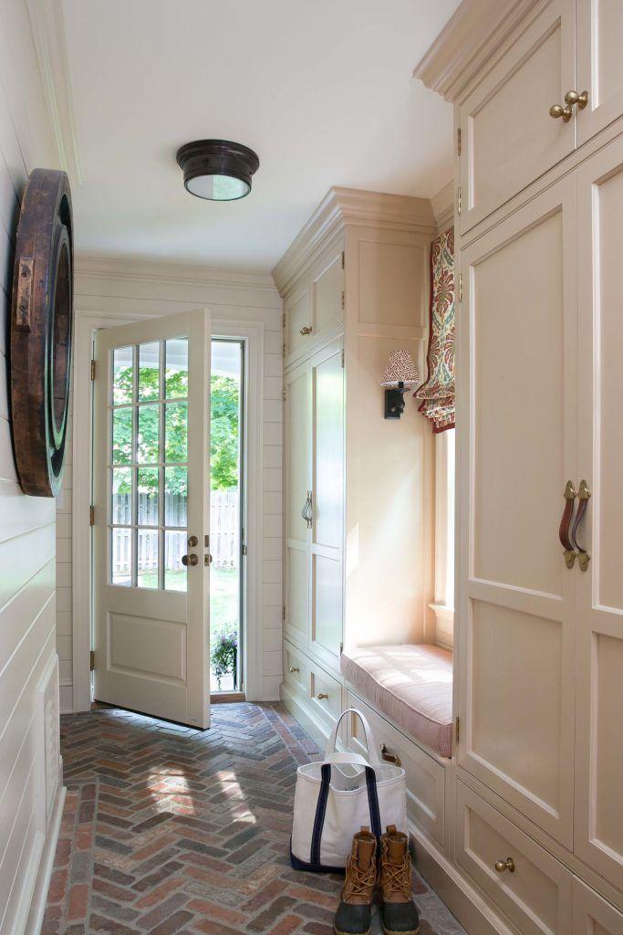 entryway, brick floor, white woodplank wall, white cabinet, pink cushion