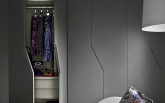 grey cupboard with zig zag lines, shelves, white chair, grey rug