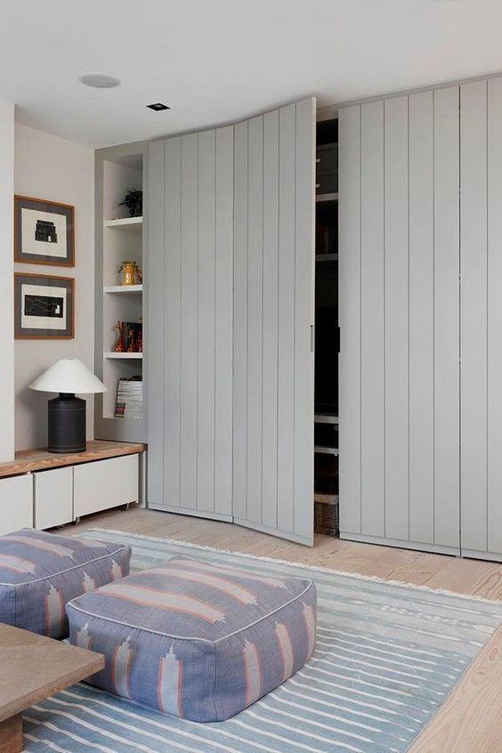 grey lined cupboard, modern look, wooden floor, blue rug, blue ottoman, wooden cabinet