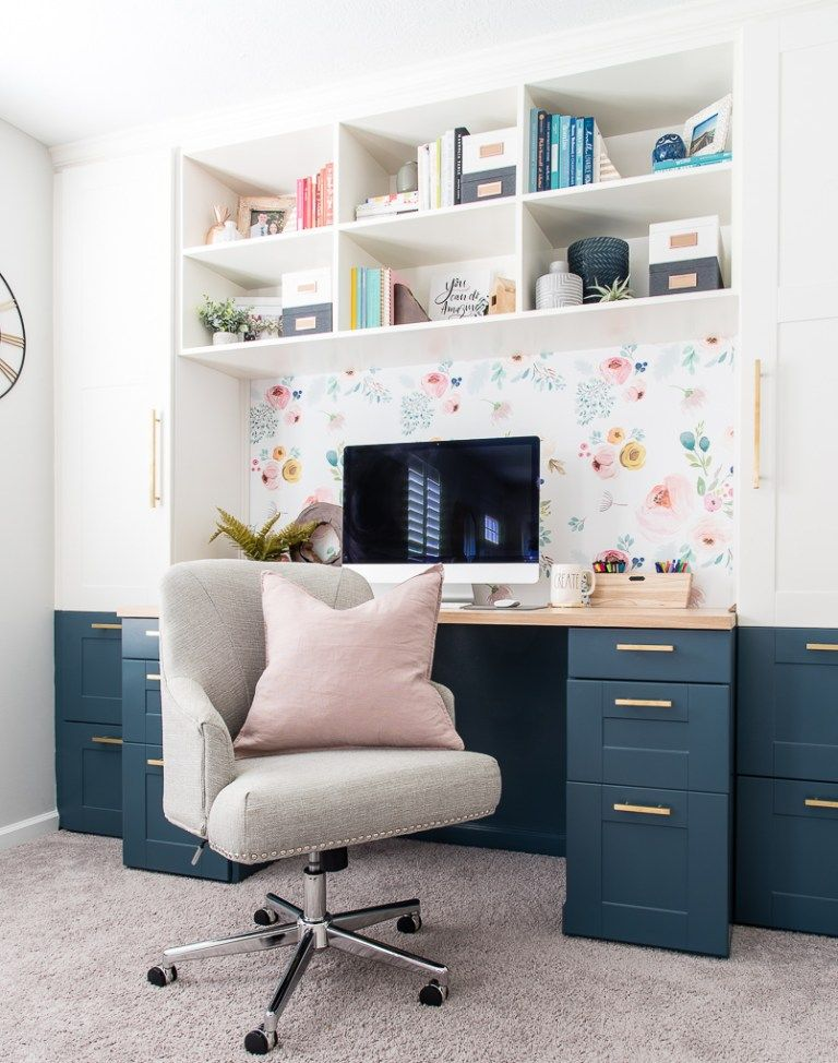 home office, brown rug, white wall, flowery accent wall, built in shelves on top, white cabinet, blue drawers, wooden counter top, grey cushion office chair