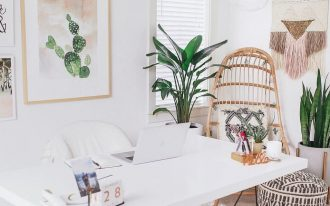 home office, white floor, white wall, rattan chair, white study table, white office chair, round ottoman, pink patterned rug, plants on white pots