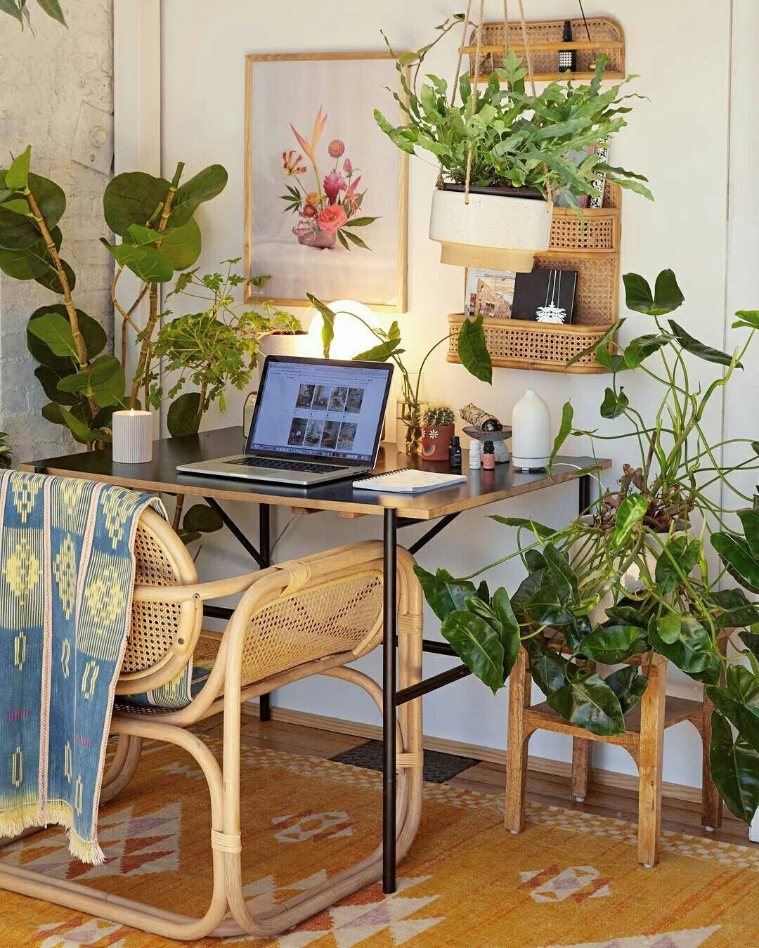 home office, wooden floor, yellow patterned rug, black simple study table, rattan chair, rattan floating shelves, wooden support, plant accessories