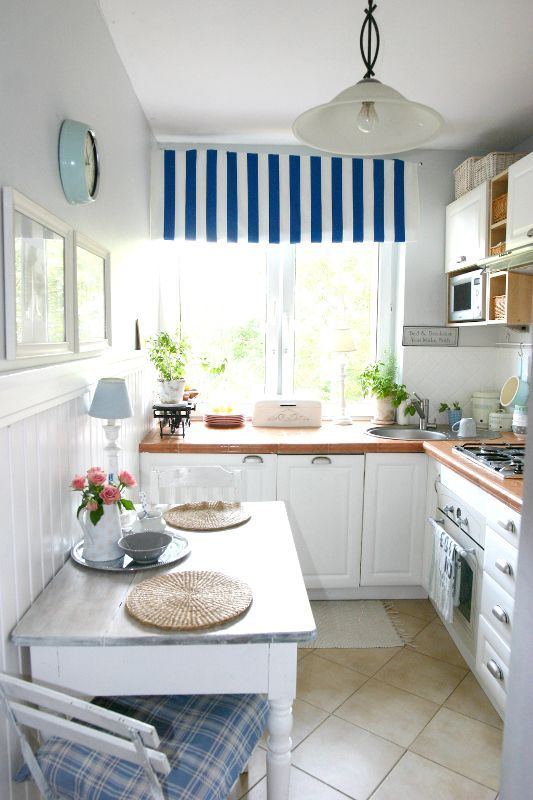 kitchen, brown floor, white cabinet, wooden counter top, white wall, white wainscotin, table, pendant