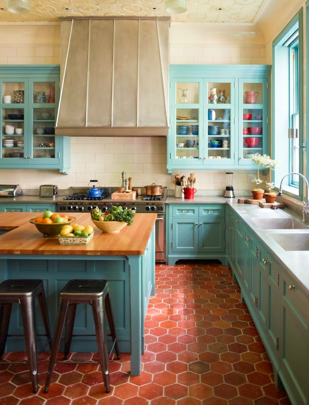 kitchen, brown hexagonal floor tiles, white subway backsplash, green cabinet with white mabrle top, green wooden island with wooden top, stools