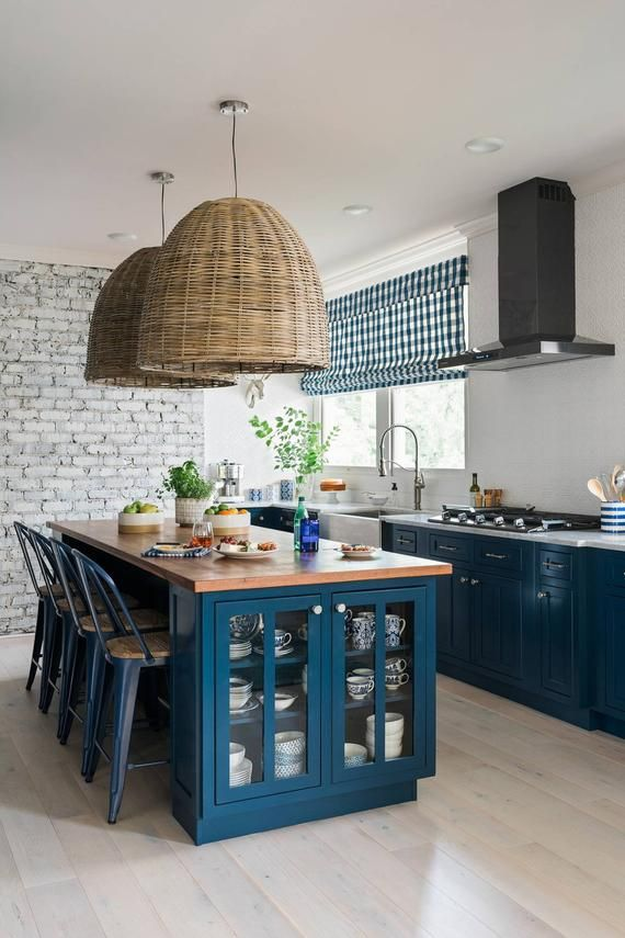 kitchen, light wooden floor, white wall, white exposed wall, rattan pendants, blue bottom cabinet, white marble counter top, blue cabinet island, wooden top, blue stools