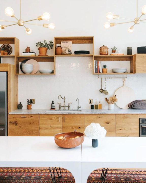 kitchen, white wall tiles, wooden bottom cabinet with white marble top, wooden boxed shelves, white pendants, white dining table