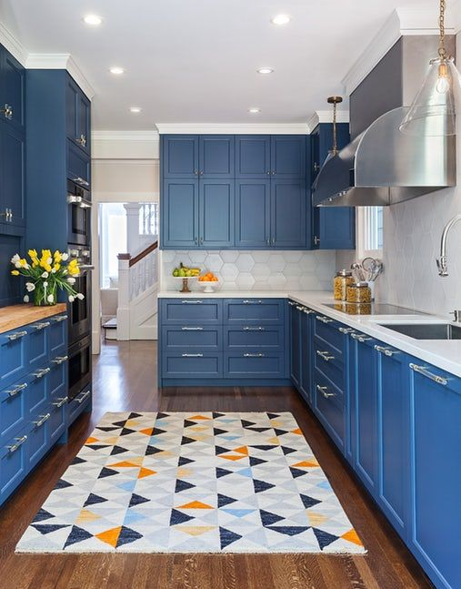 kitchen, wooden floor, blue cabinet, white hexagonal backsplash, hexagonal patterned on the rug, silver hood