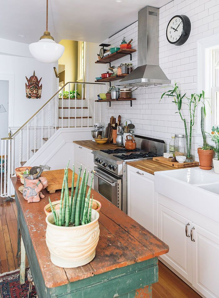 kitchen, wooden floor, white bottom cabinet, white subway walls, wooden counter top, wooden table in the middle, white pendant, silver hood