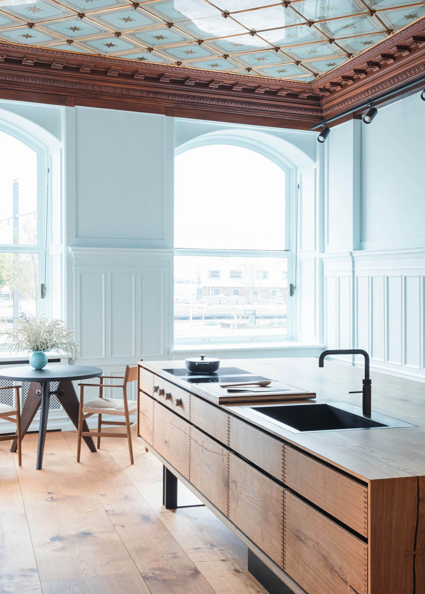 kitchen, wooden floor, white wainscoting wall, wooden cabinet, round table, wooden chairs,
