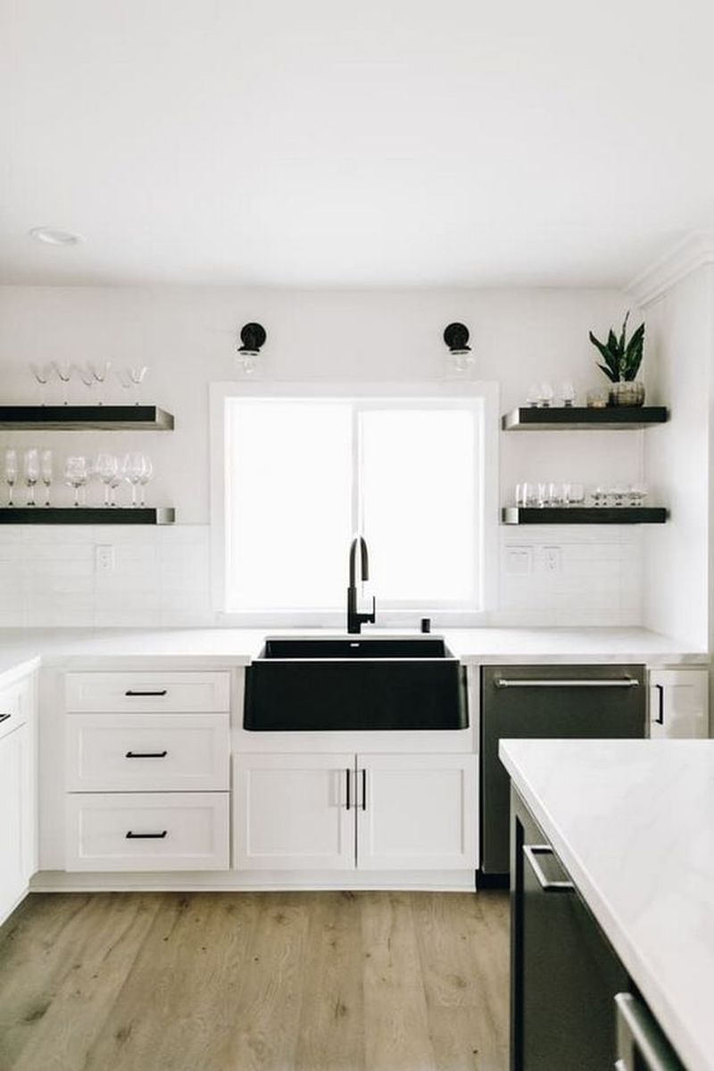 kitchen, wooden floor, white wall, white backsplash, white cabinet, black sink, black open shelves, black cabinet
