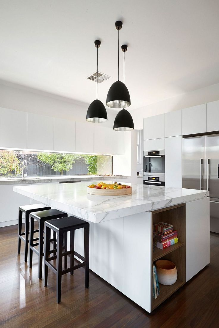 kitchen, wooden floor, white wall, white top cabinet, white marble counter top, white island, black pendants, black stools, window