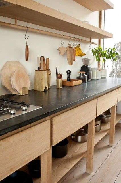 kitchen, wooden floor, wooden bottom shelves and drawers, wooden open shelves, black counter top