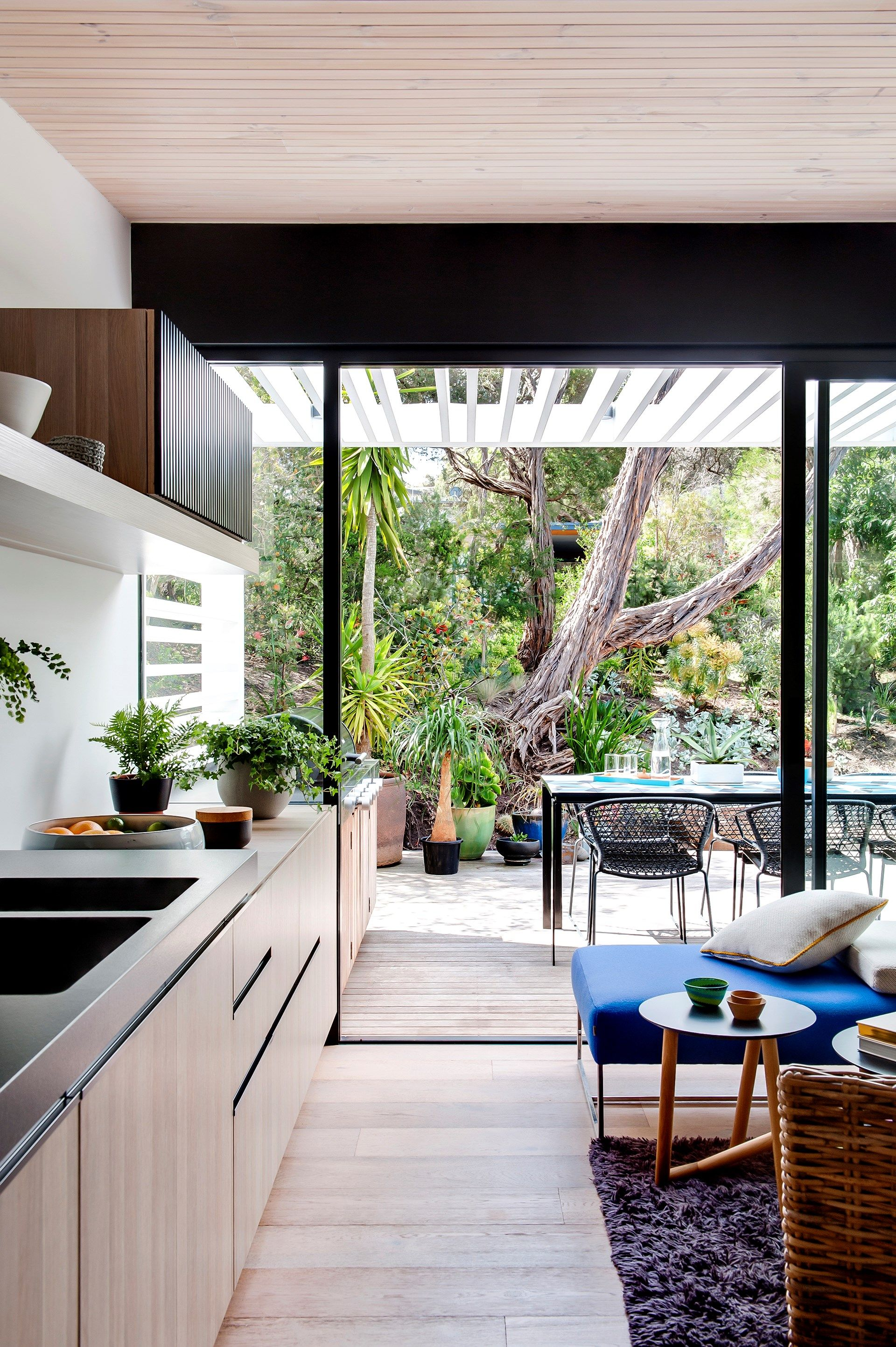 kitchen, wooden floor, wooden cabinet, white wall, glass sliding door, dining table, blue bench