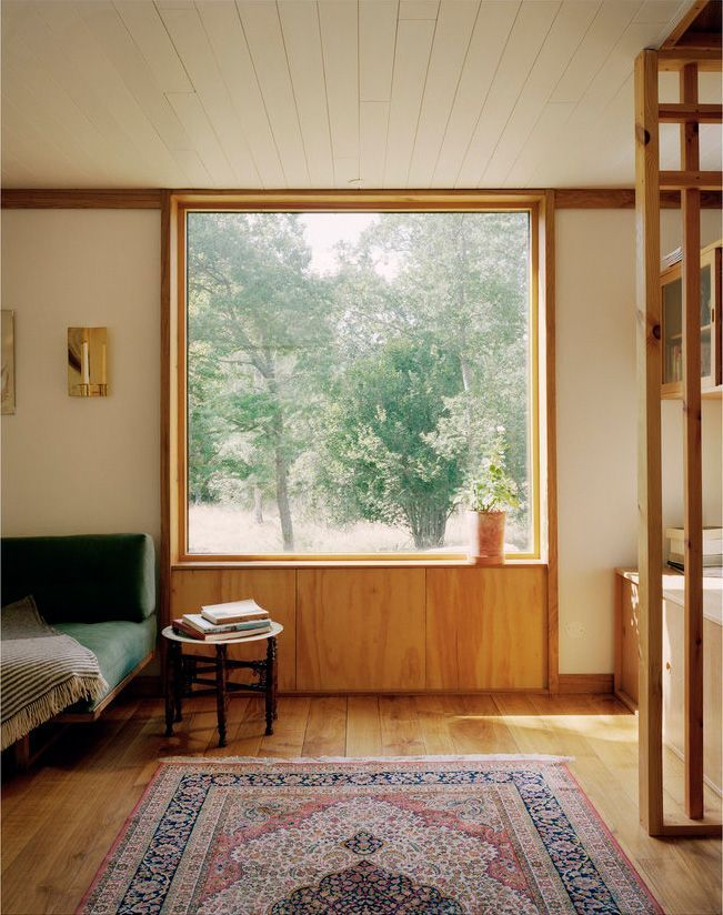 large glass window, wooden wall, white wall, wooden floor, green sofa