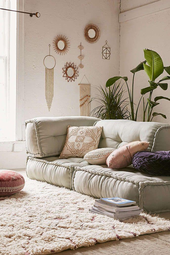 living room, brown floor, fur rug, grey floor seating, white wall, bohemian accessories, plant pot