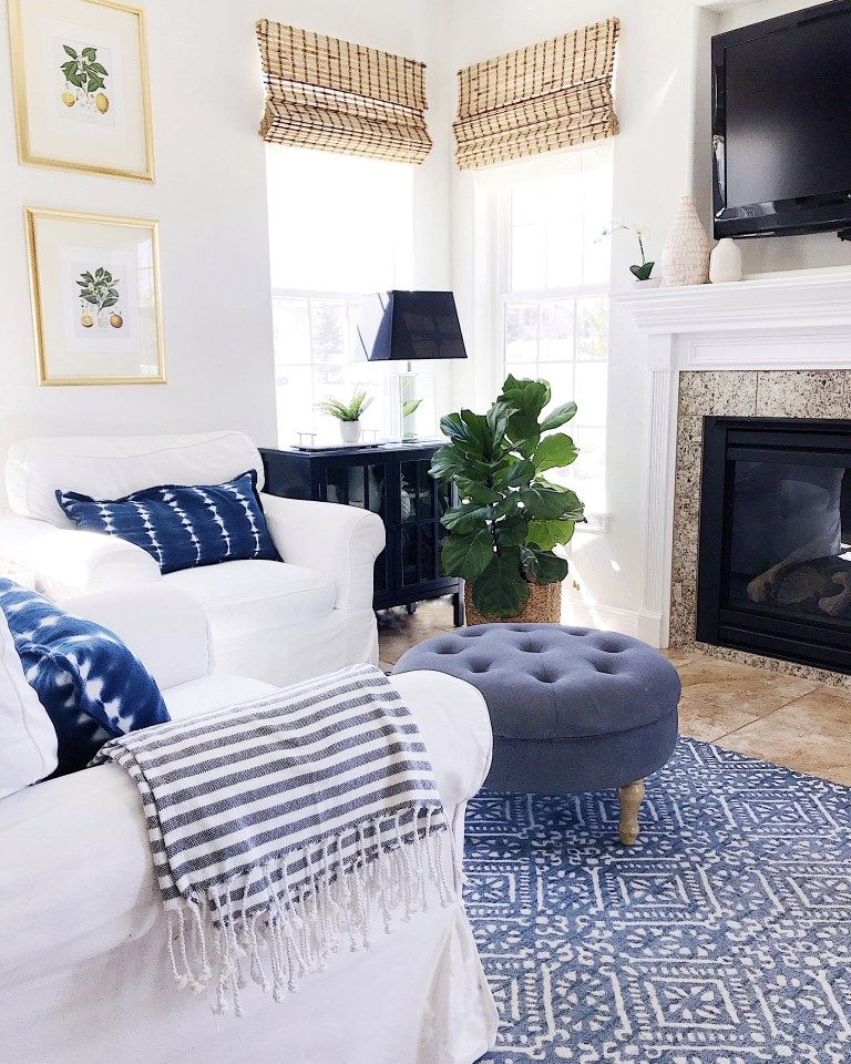 living room, brown floor tiles, blue patterned rug, blue tufted round ottoman, white sofas, black cabinet, black table lamp, fireplace