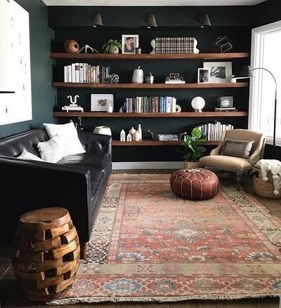 living room, dark green wall, wooden floating shelves, b;ack sofa, patterned rug, brown sofa,