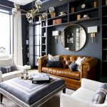 Living Room, Grey Floor, Black Wall, Indented Shelves, Brown Leather Sofa, Round Mirror, White Chairs, Blue Square Ottoman