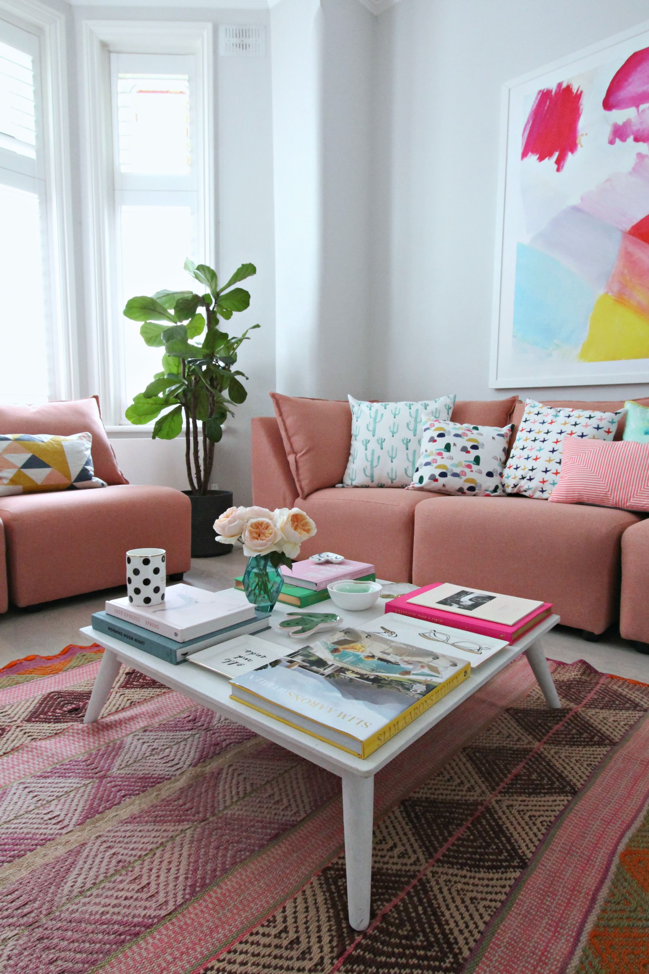 living room, grey floor, pink patterned rug, pink sofa, white wall, white coffee table