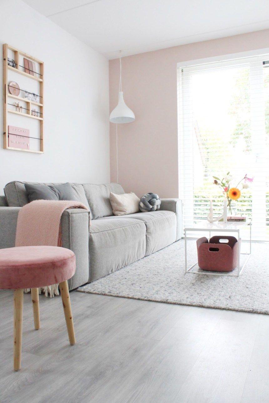 living room, grey floor, pink white wall, white pendant, grey sofa, pink velvet ottoman, white coffee table